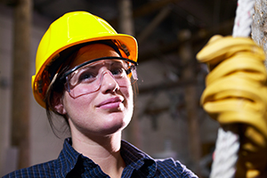 Female doing physical work in a hardhat, goggles and gloves