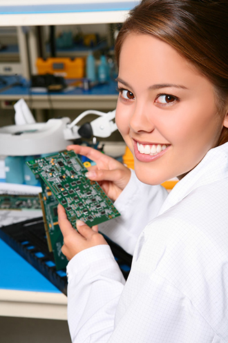 A female technician working on computer parts in a lab.