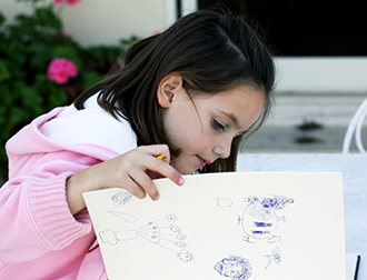 A little girl drawing a picture.
