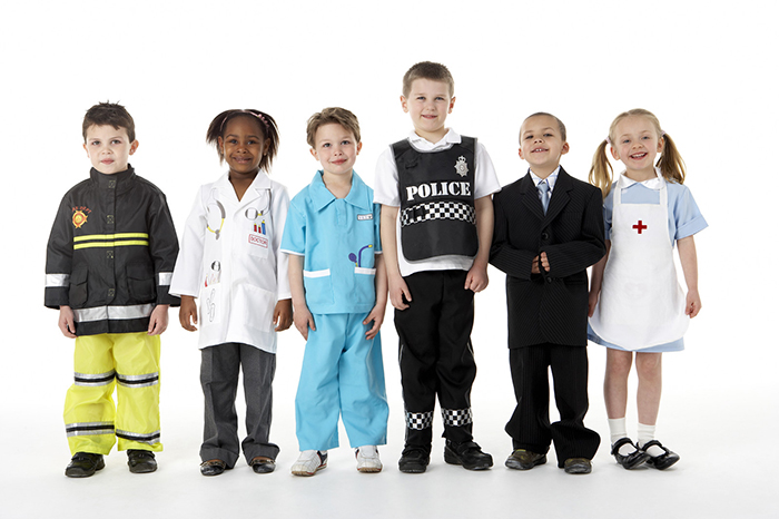 Young children dressed as different professionals such as a firemen, doctor, nurses, police, and lawyer.