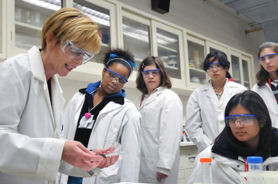 Multiracial girls in lab coats and goggles watching a female instructor