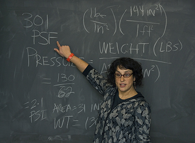 Female physics teacher at chalkboard