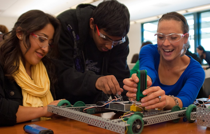 2 female and 1 male college student smiling and working on a robot together