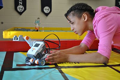 African-American girl working on robot